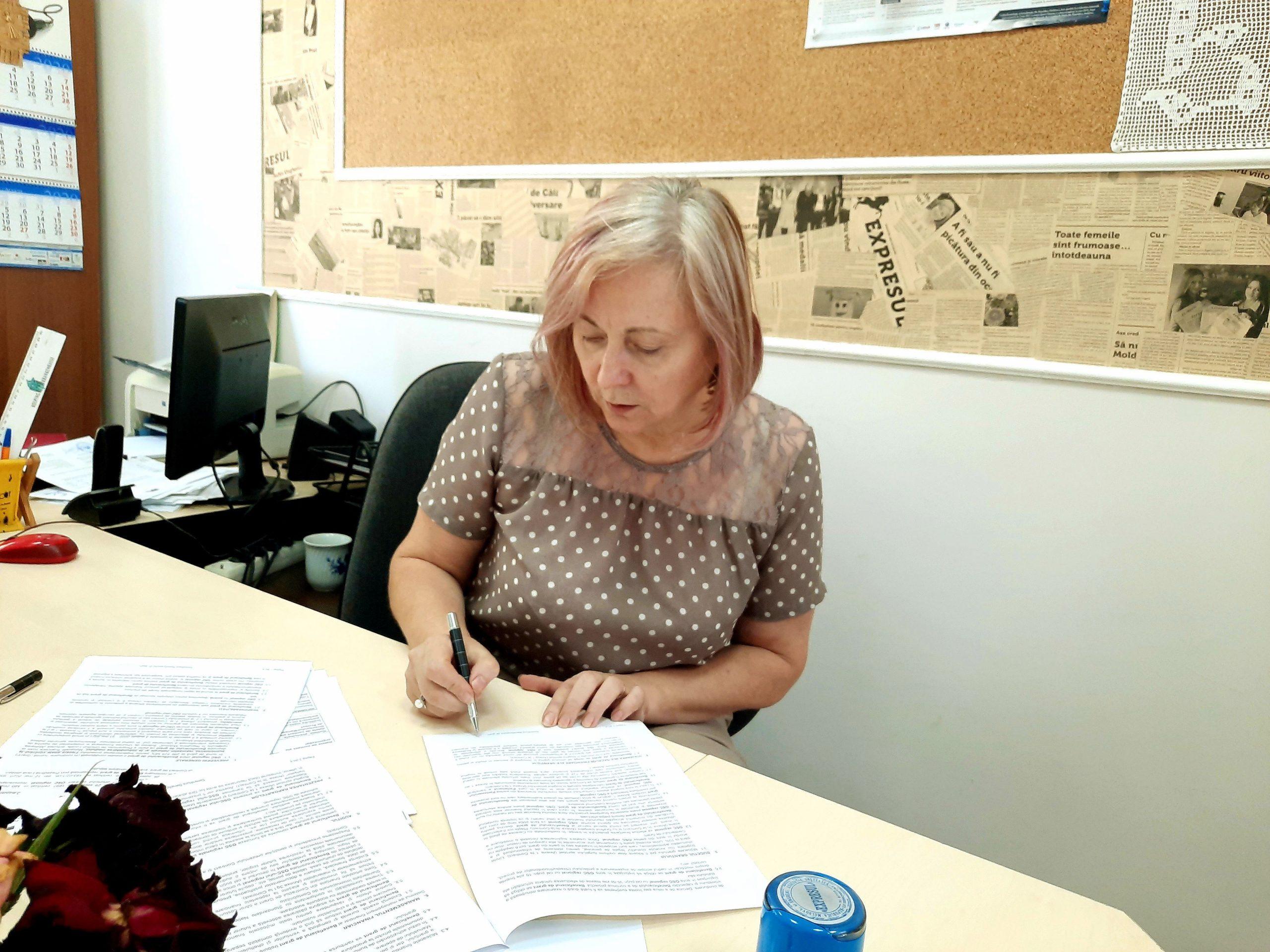 În fotografie: Lucia Bacalu- Jardan, manager de proiect, semnează contractul de grant